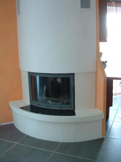 cheminee de coin  en pierre blanche et foyer galbe